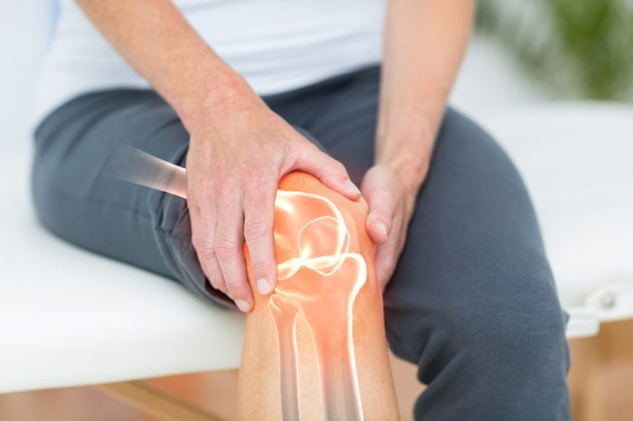 Person holding their knee, with diagram of bones underneath.