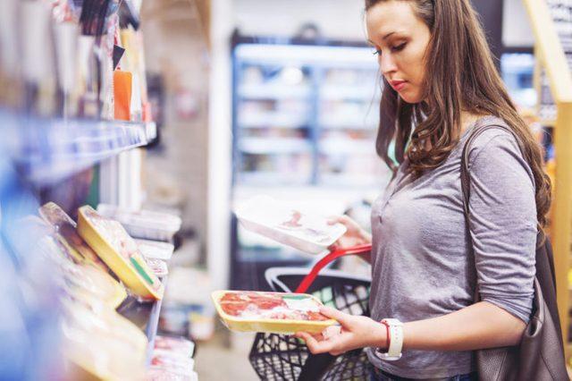 woman grocery store shopping meat frozen chicken
