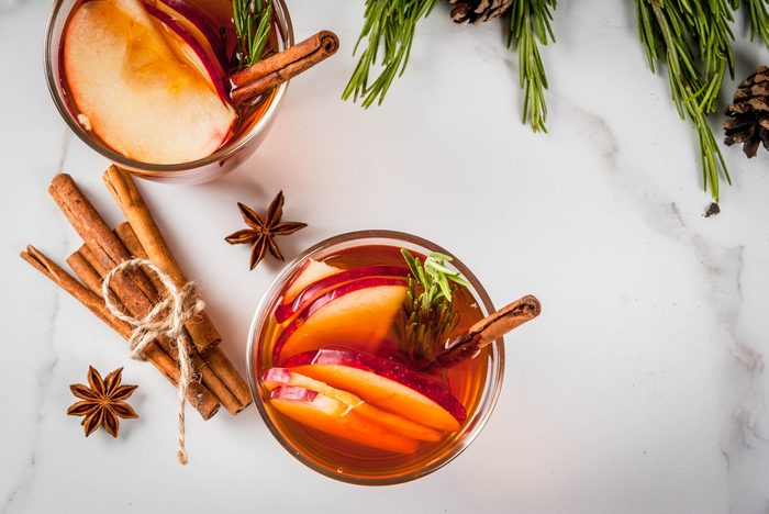 Christmas, Thanksgiving drinks. Autumn, winter cocktail grog, hot sangria, mulled wine - apple, rosemary, cinnamon, anise. On white marble table. With cones, rosemary. Copy space top view.