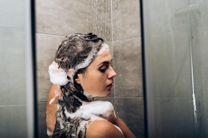 girl washing hair with shampoo in a glass shower cabin