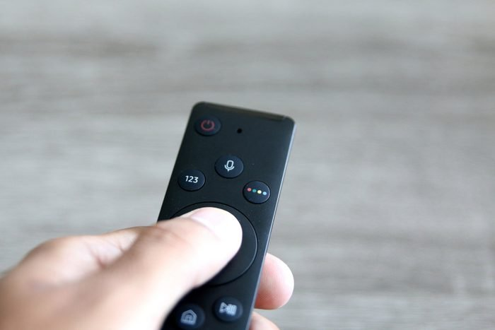 hand pressing remote control over a light grey background