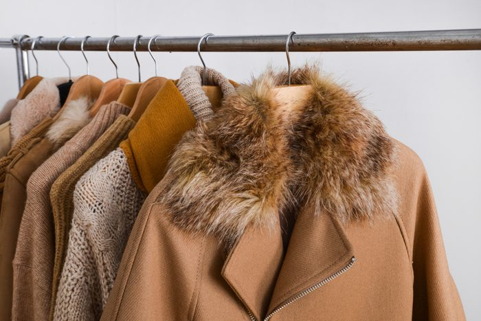 Row of women leather coat and jacket with sweater on hangers isolated