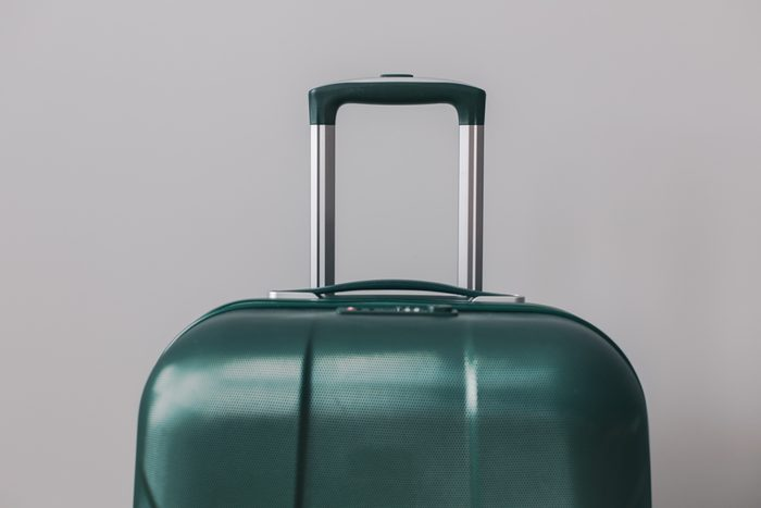 Green suitcase on gray background. Travel concept