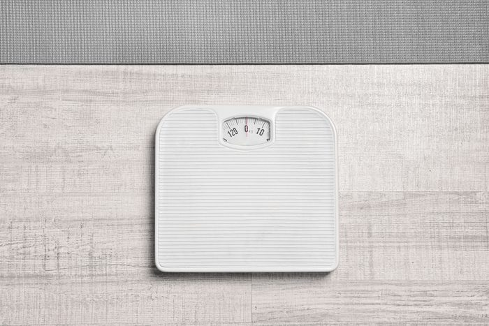 Bathroom scales and yoga mat on wooden background, top view. Weight loss concept