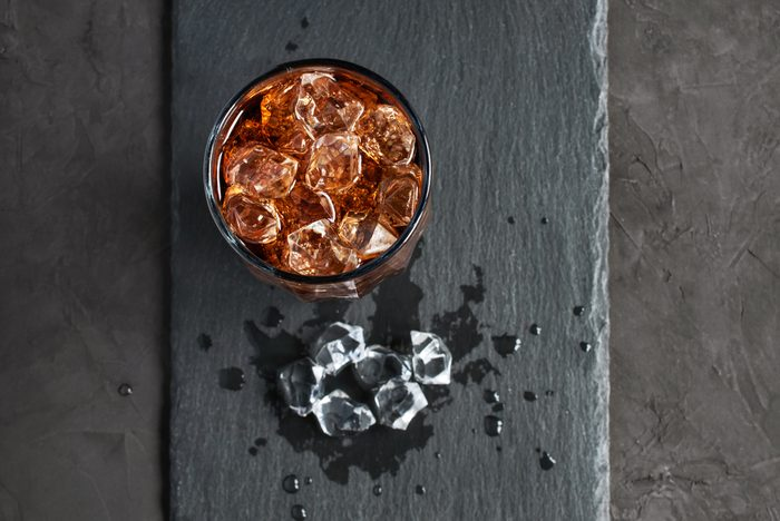Cola with ice cube on black slate board
