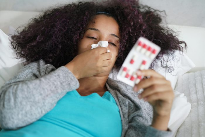 Sick african american girl with flu virus in bed at home. Ill young black woman with cold reading drug prescription for illness.