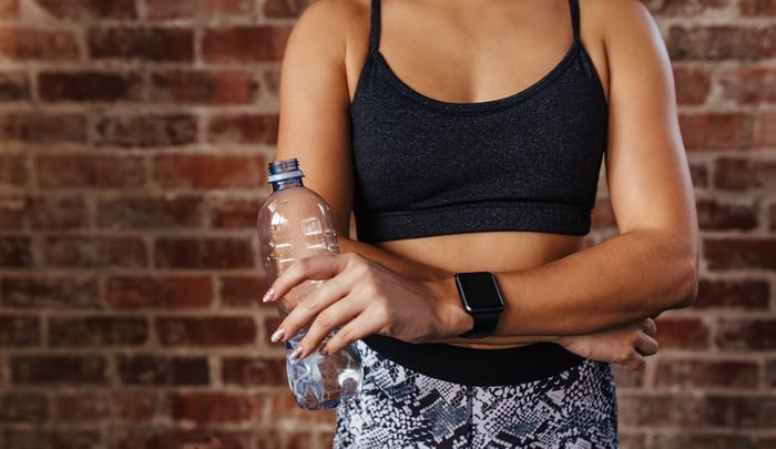 Mid section of a fit young woman holding water bottle against wall at fitness studio. Closeup of an athlete wearing a smartwatch relaxing.