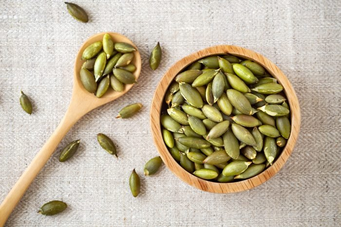 Pumpkin seeds in wooden bowl and spoon, top view