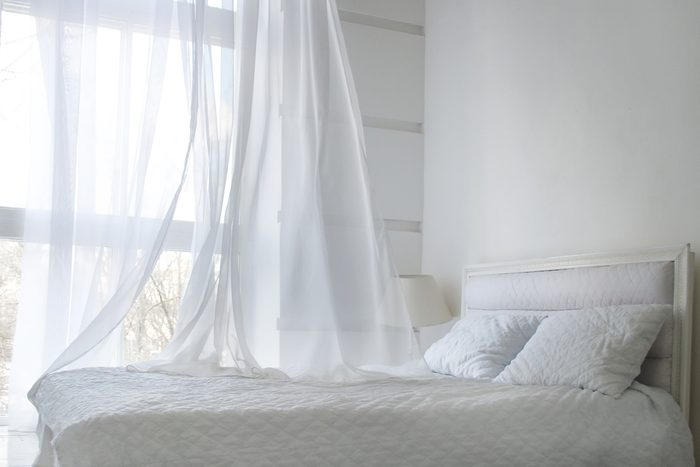 White themed bed sheets and white curtain in the morning, bedroom interior