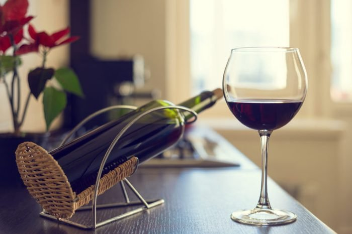 wine bottle and glass of red wine on table at home