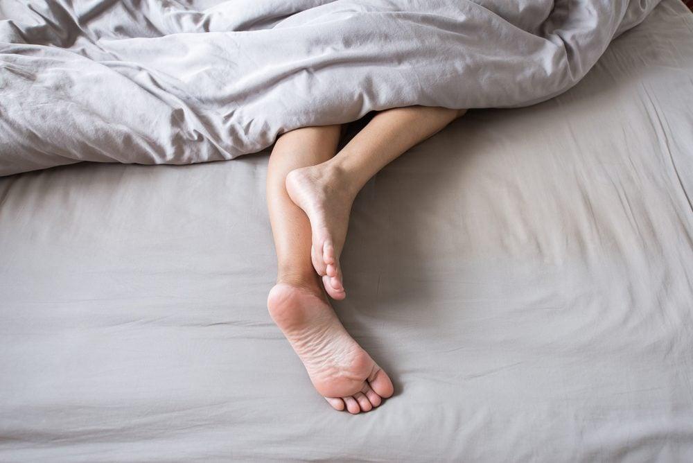 Barefoot en been onder deken op bed
