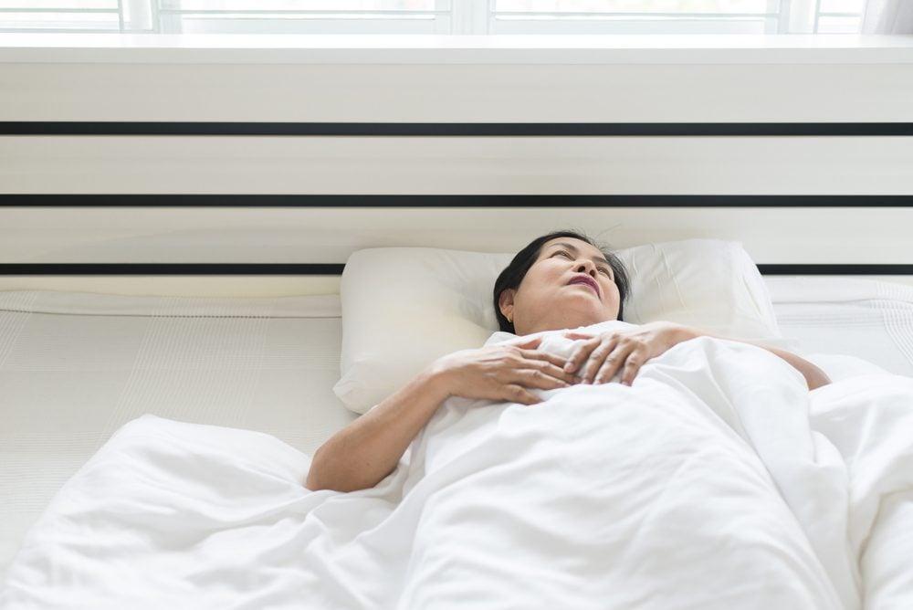 Eldere Aziatische vrouw depressief heeft hoofdpijn en voelt zich serieus genomen in slaapkamer