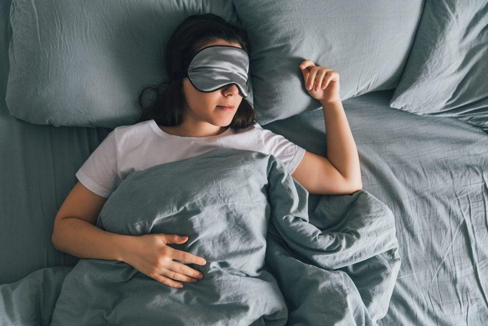 vrouw slaapt in ooglapje in grijs bed. copy space