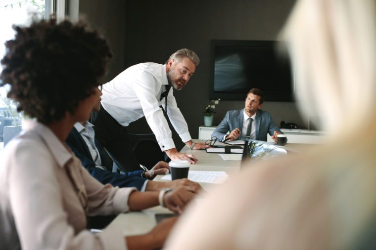 Senior executive explaining something to his team in a meeting. Business people during a meeting in board room.