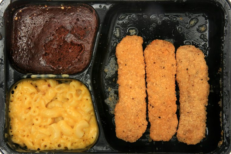 "frozen microwaveable ""tv dinner"" ""Chicken Fingers Meal"" with ""Breaded Chicken Patties"", ""Macaroni & Cheese Sauce"", and a ""Fudge Brownie"" isolated on white with room for your text"