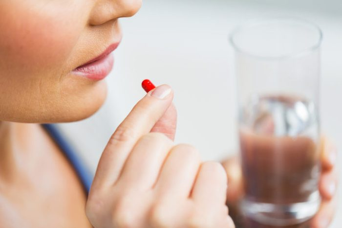 Close up of woman taking in pill.