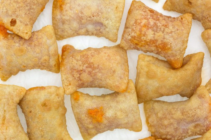 Several bite size pizza rolls on a white paper napkin that have been microwaved.