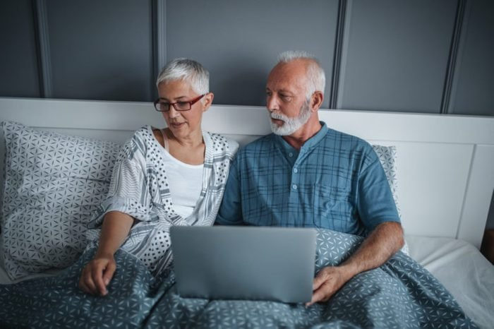 Mature couple using laptop while in bed