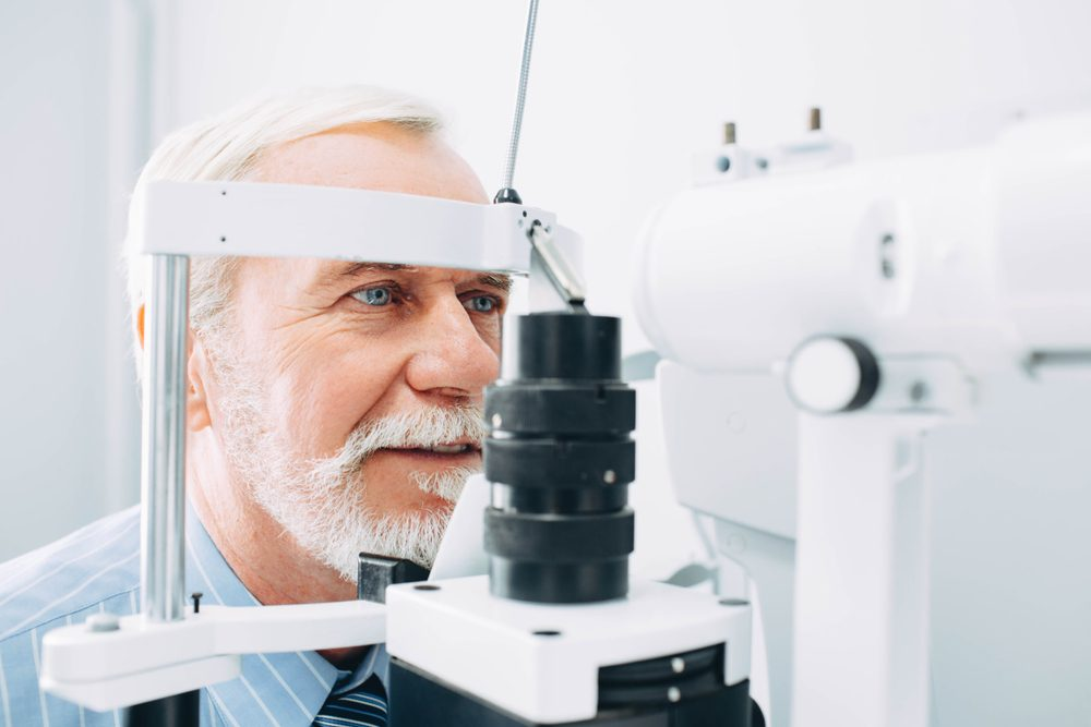 Senior man receiving eye exam at clinic, eyesight examination aged people