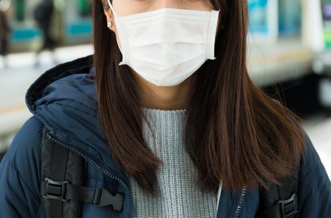 Woman wearing face mask at train station