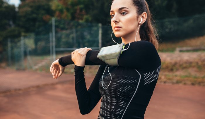Portrait of a beautiful sports woman stretching hands outdoors. Caucasian female warming up.
