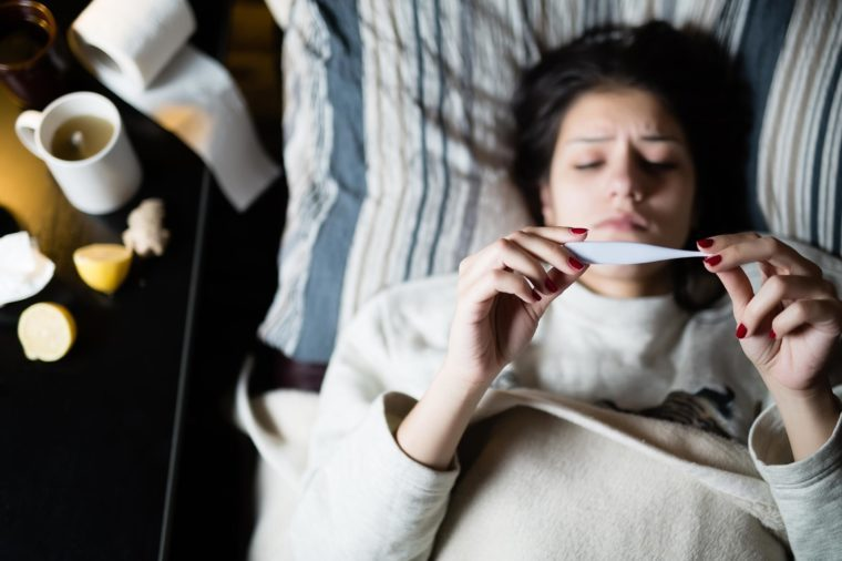 sick woman thermometer flu bed