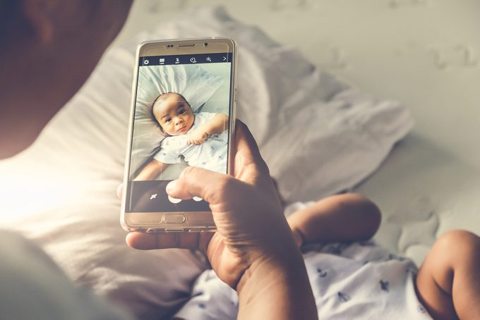 High angle shot of happy mother taking picture her baby boy in bed with smart phone at home.