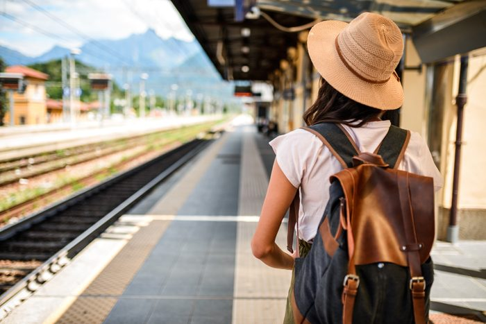 rear view of young woman waiting for train to arrive