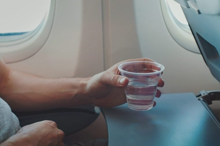 Passenger drinking water in airplane during flight. Close up of hand holding glass in plane.