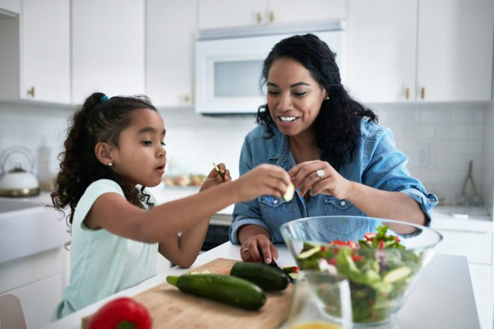 mother and daughter preparing healthy food salad