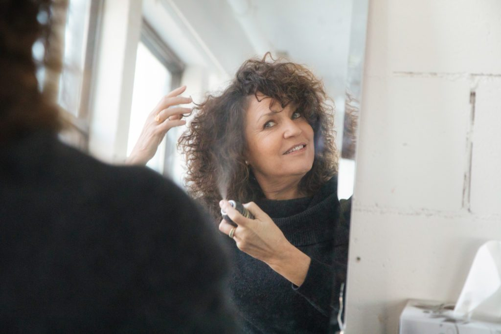 woman spraying hairspray into her hair