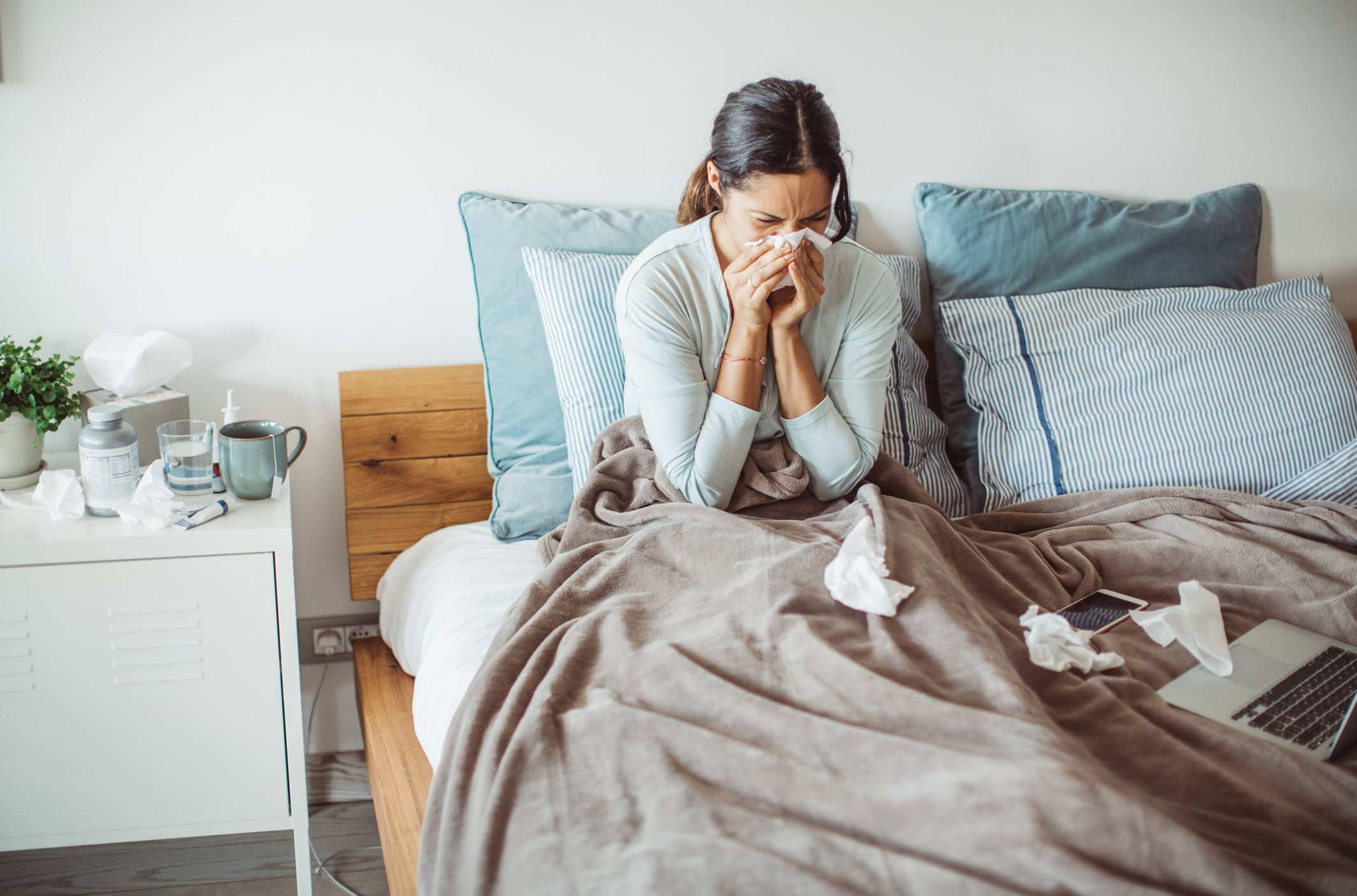 woman sitting in bed blowing nose