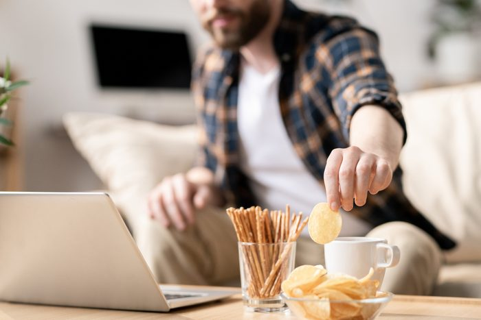 man grabbing snack while working on laptop