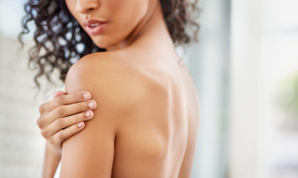 side cropped shot of woman rubbing skin