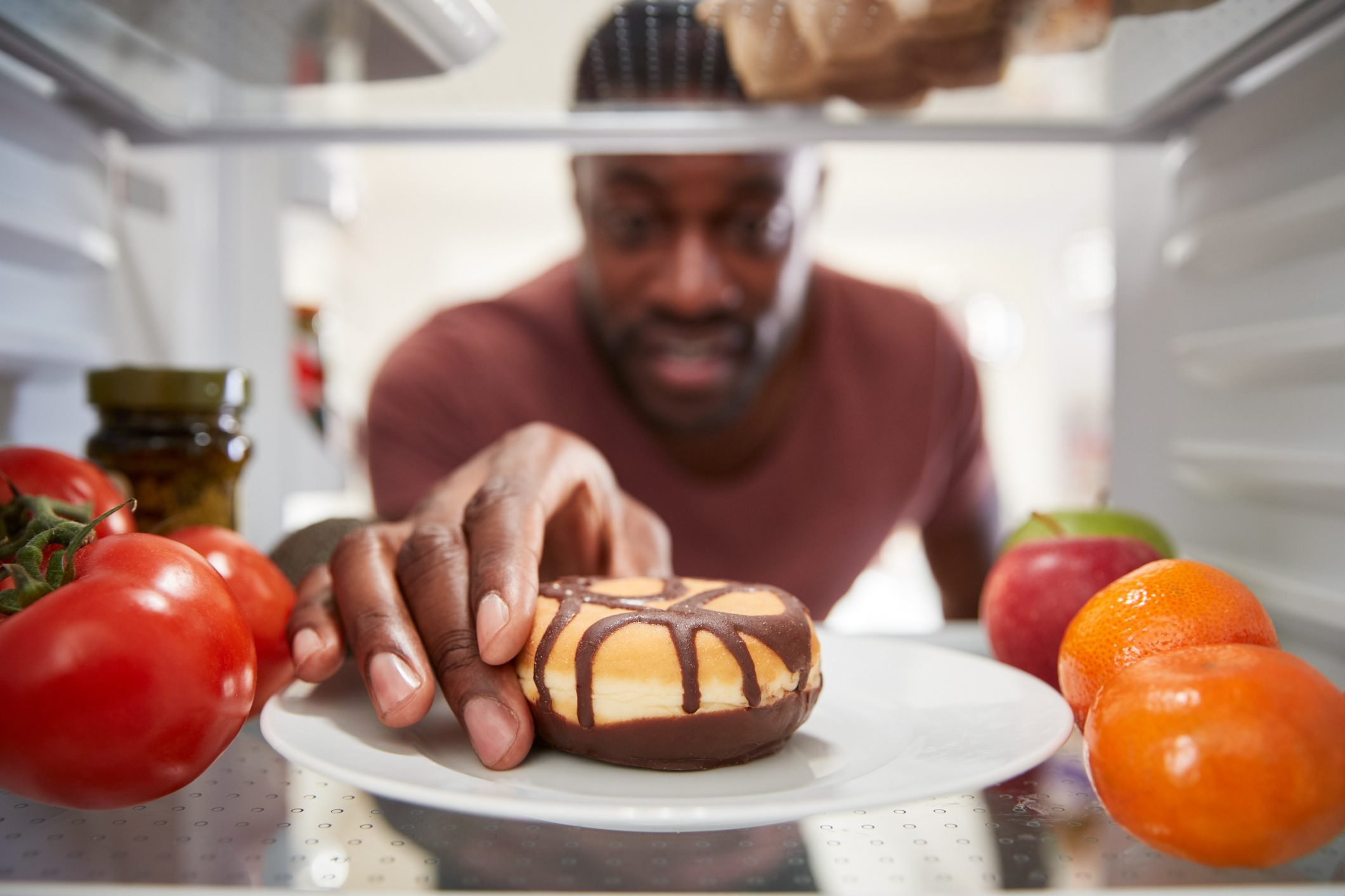view from inside of refrigerator as man reaches for donut
