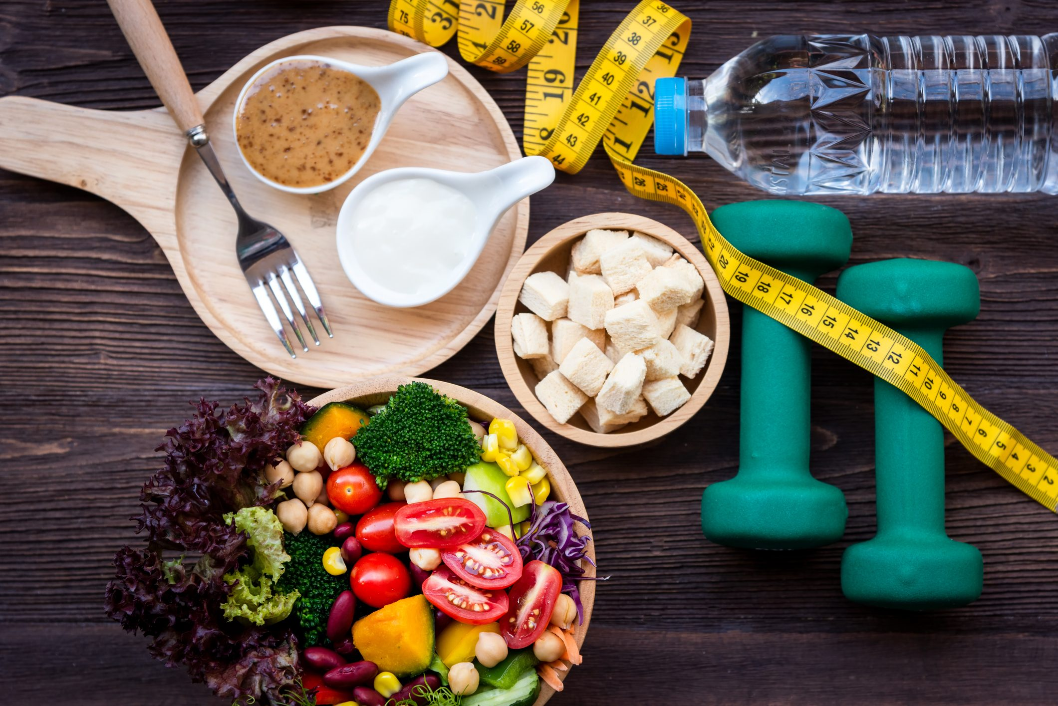 fresh vegetables, tofu, measuring tape, weights, and watter; weight loss concept