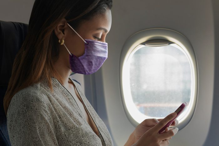 woman sitting on airplane with face mask on