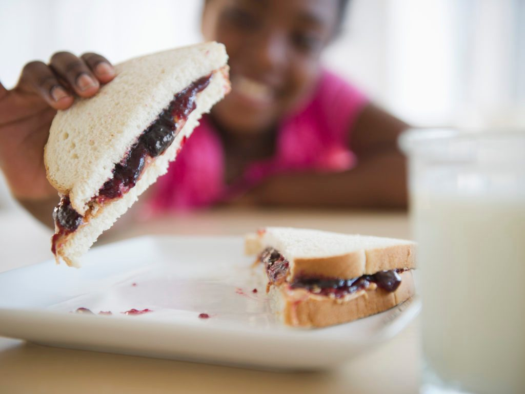 little girl holding peanut butter and jelly sandwhich
