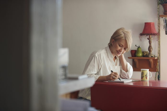 older woman writing in journal at desk