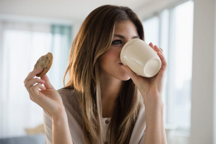 woman drinking a cup of coffee and eating a cookie