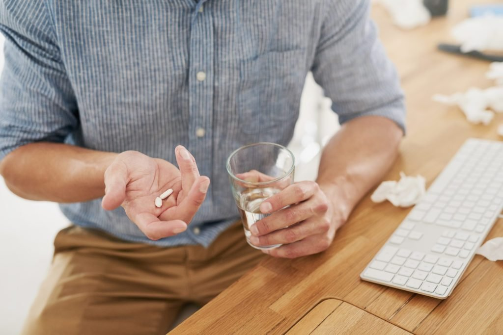 man holding a glass of water and two white pills