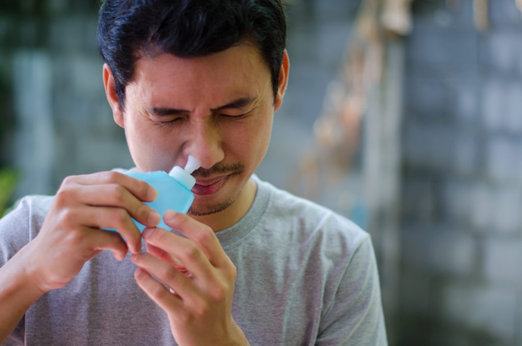 man using a saline nasal rinse device