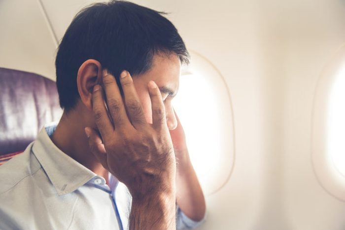 Male man airline flight passenger having ear pop on the airplane while taking off