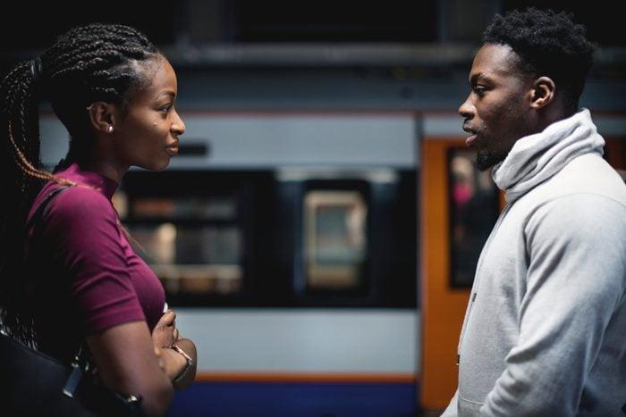 Couple having an argument on the subway platform