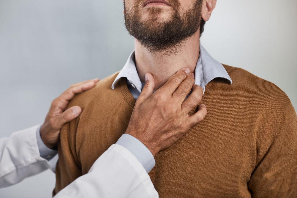 doctor's hand touching a man's neck