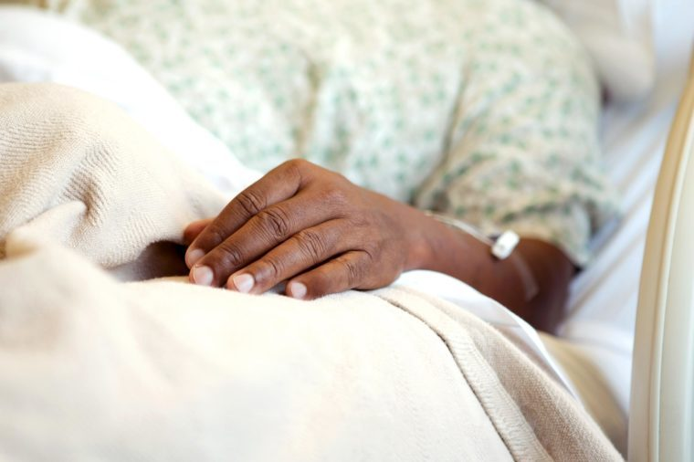 hospital bed hand gown african man