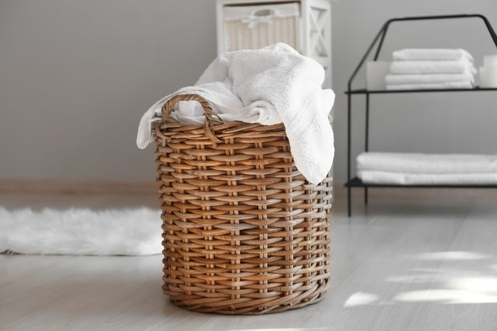 Laundry basket with dirty towels on floor