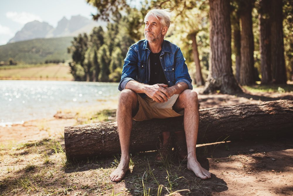 Portrait of a senior man sitting on a log near lake and looking away. Mature man sitting alone on lake.