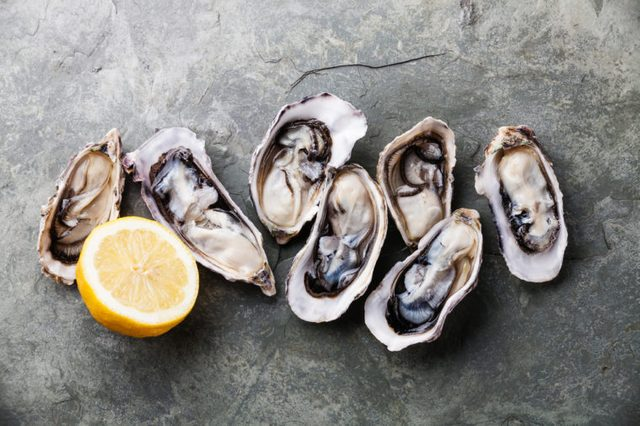 Opened Oysters on stone slate plate with lemon