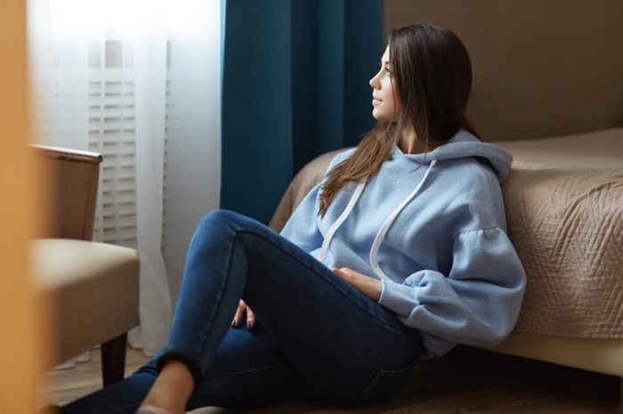Indoor shot of thoughtful dark haired woman dressed in blue sweatshirt, jeans, sits on floor near bed, looks thoughtfully at window, poses in cozy bedroom at modern apartment. Domestic atmosphere